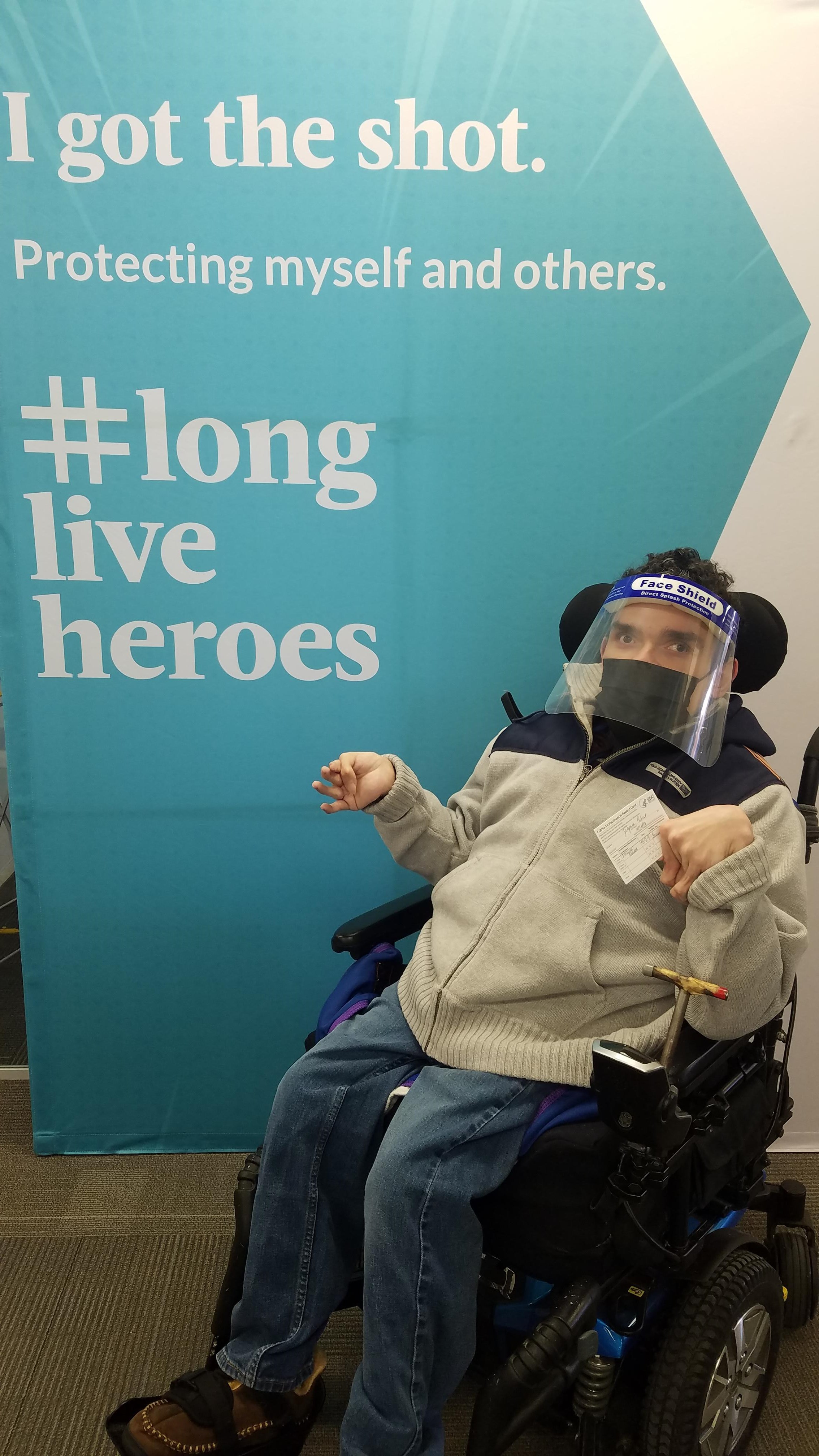 """Robert Zotynia sits in his wheelchair with a face mask and face shield on posing in front of a sign that reads """"I Got the Shot. Protecting Myself and Others"""""""